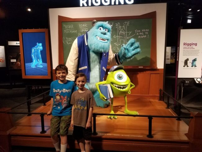 boys posing with Mike & Sully from Monsters Inc.