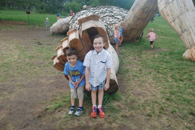 Two boys posing with giant troll foot