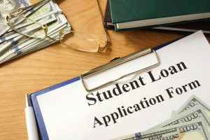 Student loan form with dollars and books.