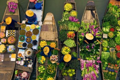 Floating market vendors, Bangkok, Thailand Floating markets are a common tradition throughout Southeast Asia where the numerous rivers and waterways are a primary means of transportation and commerce between villages. In this overhead view, Bangkok vendors draw their boats together to exchange a colorful, tasty array of goods, Thailand.