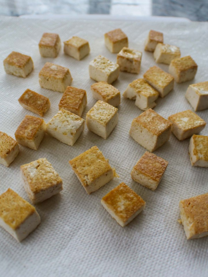 close up of fried tofu cubes draining on towels