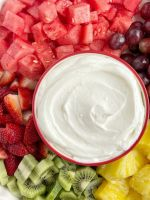 Fruit dip recipe with coconut cream and freshly whipped cream on a plate with fresh cut fruit.