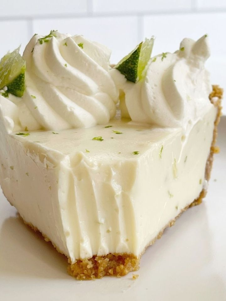 A slice of key lime pie with a bite taken out of it with a fork.