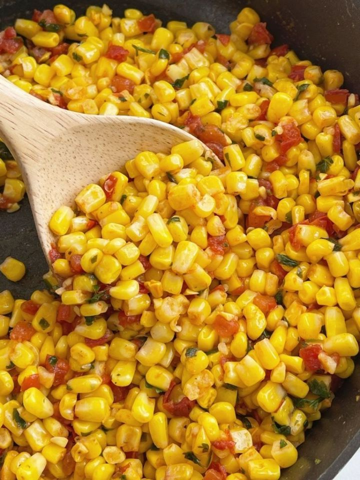Southwestern Corn with a wooden spoon scooping some out.