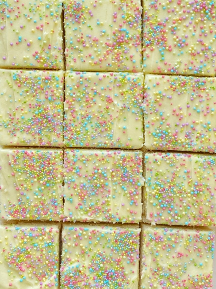 Sugar Cookie Bars made in a 9x13 pan that are soft, sweet and topped with the best (not too sweet) frosting and sprinkles! Change up the frosting color and sprinkles for any occasion.