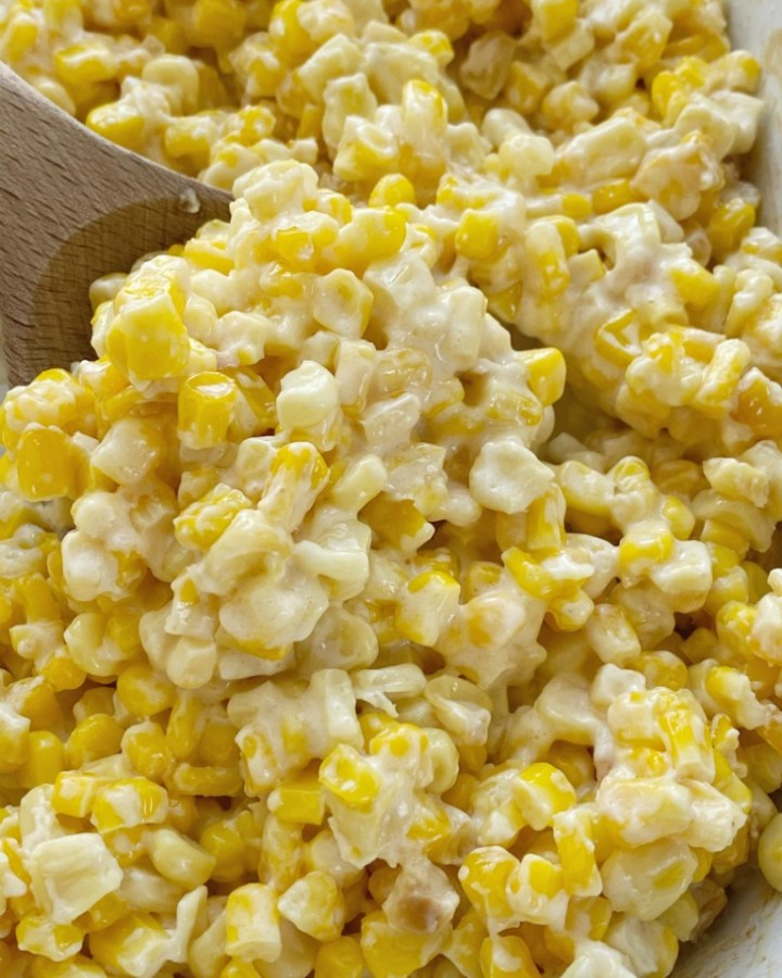A close up picture of slow cooker creamed corn with a wooden spoon.