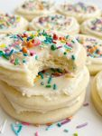 A stack of sugar cookies with a the top cookie having a bite taken out of it.