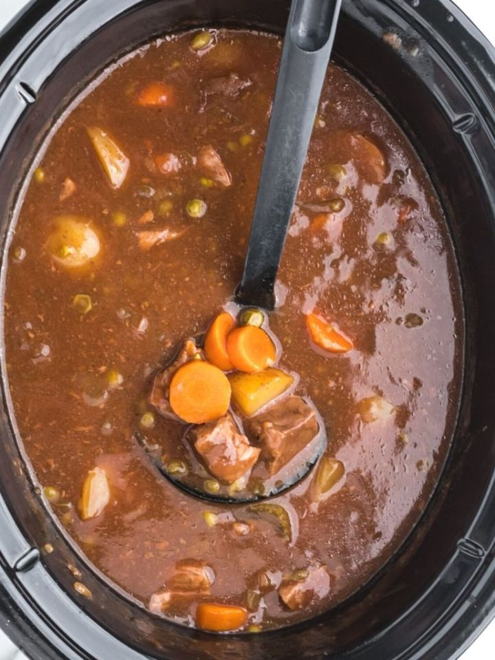 Slow cooker full of beef stew with a black ladle in it.