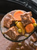 A scoop of apple cider beef stew with the slow cooker in the background.