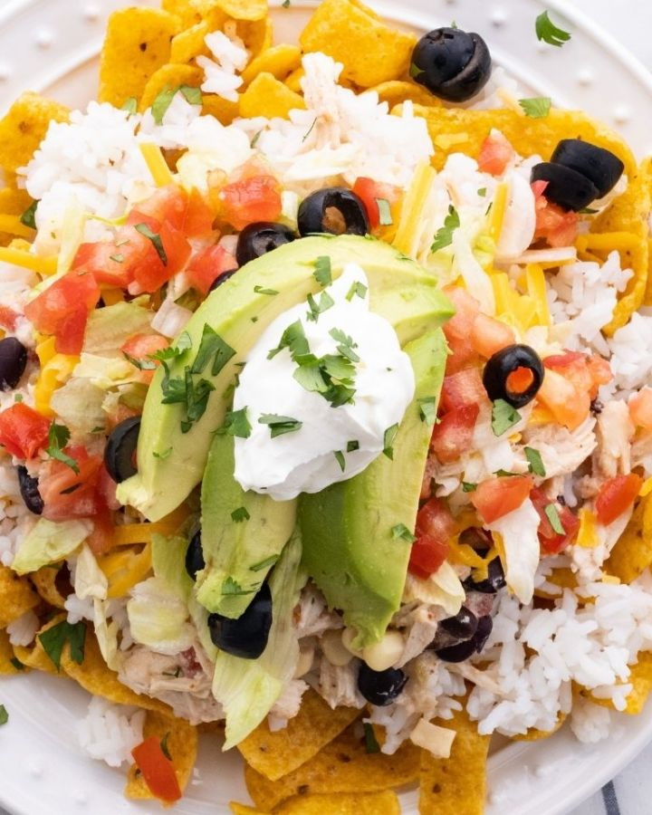 A picture of Fritos chips, topped with rice, and topped with chicken Mexican Haystacks that are made in the slow cooker.