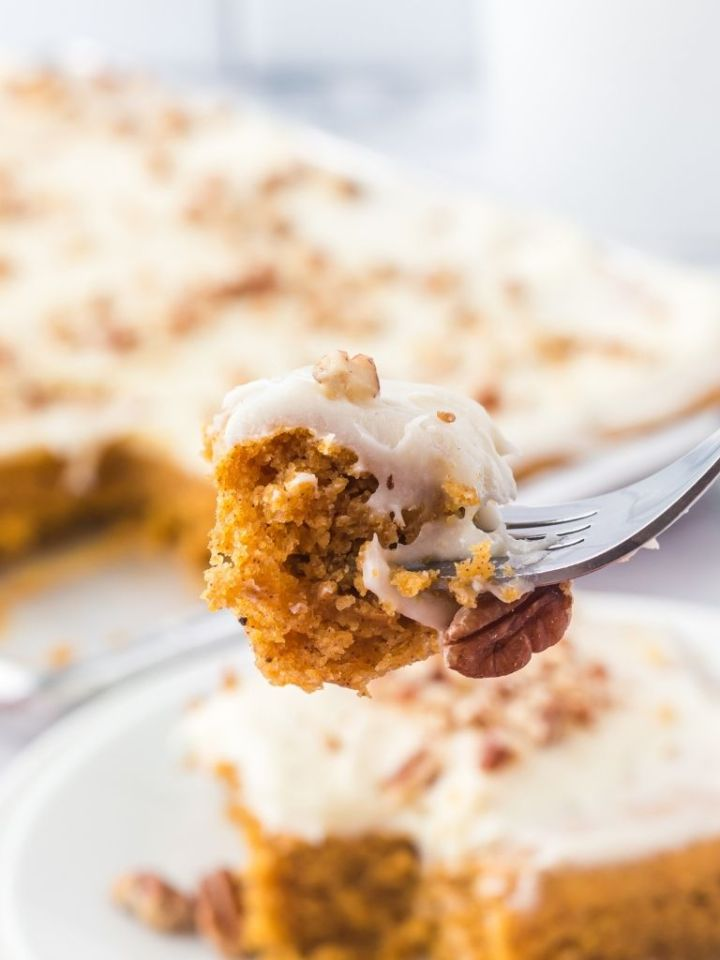 A bite of pumpkin cake on a silver fork with some cake blurred in the background too.
