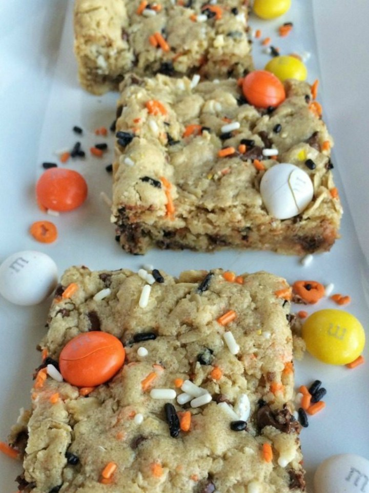 These festive candy corn m&m Halloween cookie bars are sure to be a hit! A soft, thick, chewy cookie bar loaded with candy corn m&m's, Halloween sprinkles, chocolate chips and peanut butter. Perfect treat for Halloween parties or just because.