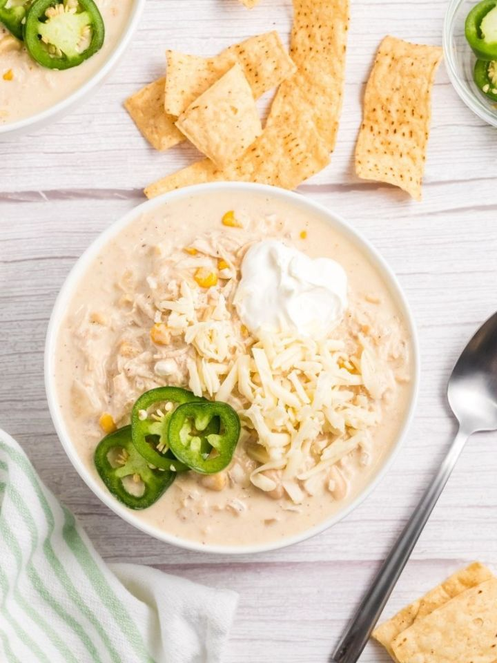 White chili inside a white bowl on a tables cape with chips and jalapeño slices.