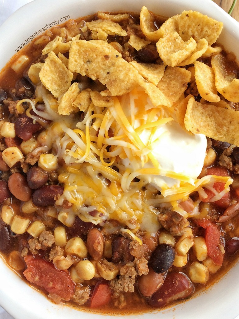 Santa fe chili is cooked in the slow cooker all day for ultra tender and flavorful chili. Brown some ground beef & onion, and add some cans into the crock pot. That's it! Serve with sour cream, shredded cheese, and fritos chips for the ultimate chili dinner