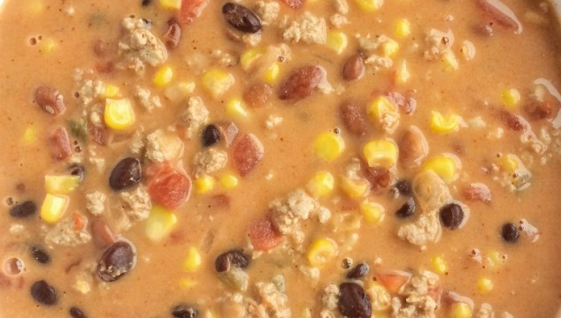 This cheesy taco soup is so easy. Brown some ground turkey with spices, add 6 cans, and some Velveeta cheese. Super creamy, cheesy, delicious, and quick dinner!