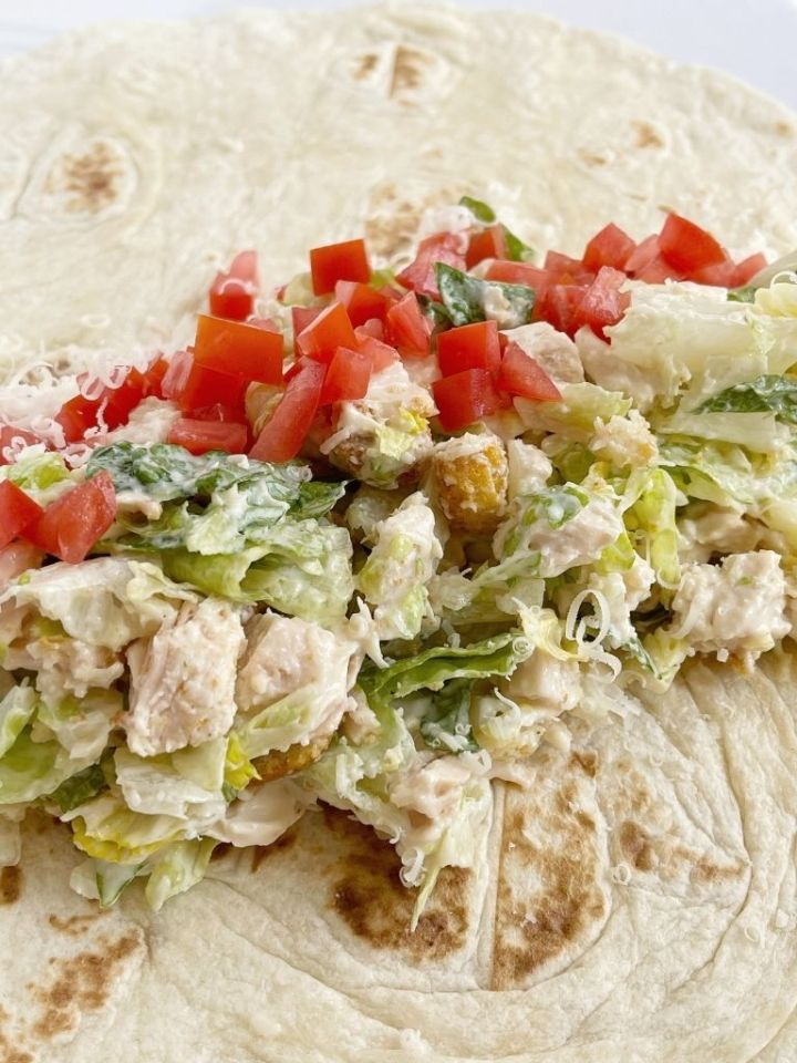 Chicken wraps with Caesar salad dressing and chicken on a flour tortilla.