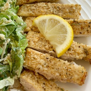Crispy Baked Lemon Parmesan Chicken | Baked Chicken with a crispy lemon parmesan coating. Boneless skinless chicken breasts, fresh lemon, garlic, Italian breadcrumbs, and parmesan cheese make for the most flavorful crispy baked coating on chicken. It's a family favorite!