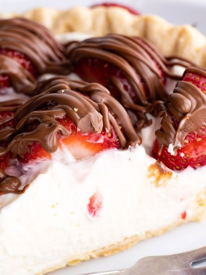 A close up of strawberry pie with a chocolate drizzle over top.