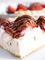 A slice of cheesecake cream pie topped with strawberries and chocolate drizzle.