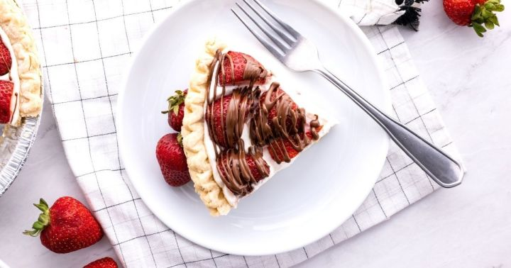 A horizontal image (overhead) of a slice of strawberry pie on a white plate with a fork.