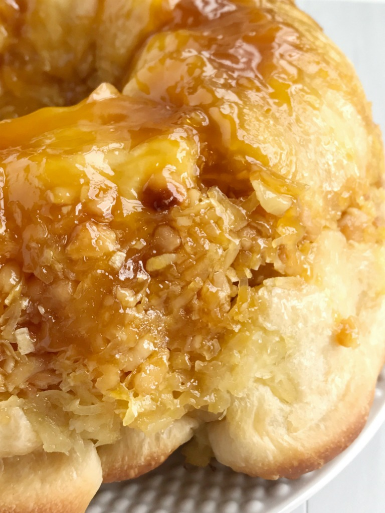 This easy, no yeast needed tropical monkey bread is loaded with Hawaiian flavors! Flaky, buttery rolls covered in coconut pudding, macadamia nuts, coconut, sugar, and pineapple. Prepare the night before for easy overnight sweet bread in the morning. This stuff is so delicious and makes for a great dessert or extra special breakfast.
