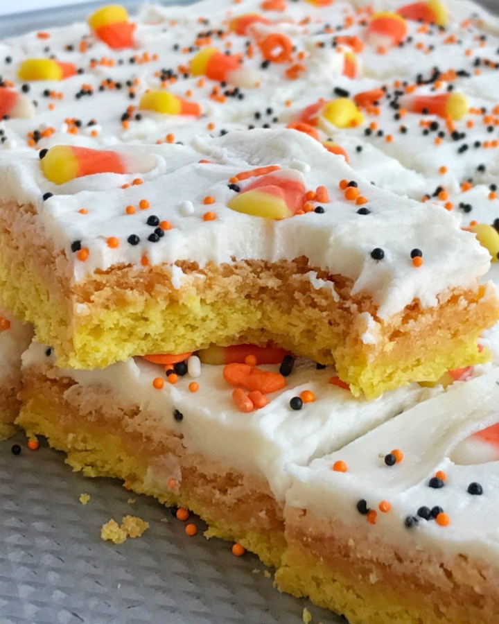 Candy corn sugar cookie bars are the best way to celebrate Halloween. Sugar cookie bars made in a sheet pan so there is plenty for everyone. Layered in yellow & orange sugar cookies and then topped with a white cream cheese icing and decorated with candy corn and Halloween sprinkles! These are so addictive and will be the hit of any party.