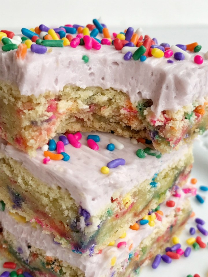 Soft, thick, and chewy funfetti sugar cookie bars loaded with sprinkles and topped with a sweet buttercream frosting! Change up the frosting and sprinkles for any Holiday or celebration. These are so sweet and delicious | togetherasfamily.com #sugarcookiebars #dessert