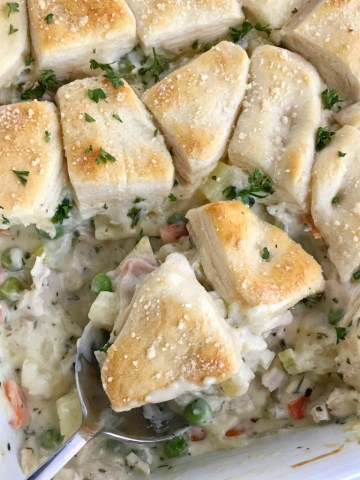 Creamy chicken pot pie casserole is the ultimate comfort food recipe. Vegetables and chicken simmer in a creamy chicken broth and then they're topped with flaky buttermilk biscuits. Creamy, warm, comforting, homemade goodness in one casserole pan   www.togetherasfamily.com #casserolerecipes #recipe #dinnerrecipes #chickenrecipes #chickencasserole #chicken #comfortfood
