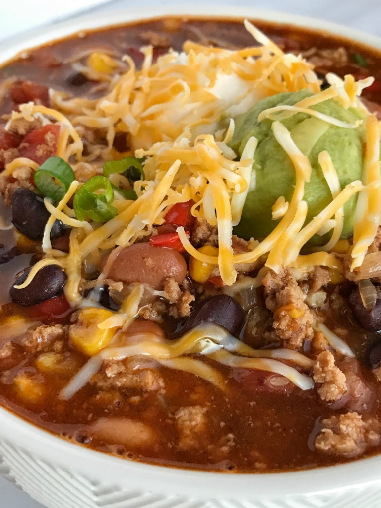 Southwestern Turkey Chili Taco Soup | Turkey chili taco soup loaded with all the best southwest flavors. Turkey taco meat, chili beans & spices, corn, tomato, and taco soup seasonings all combine for one deliciously hearty chili taco soup. It's the best of both worlds. Top with cheese, sour cream, guacamole, and crushed tortilla chips | www.togetherasfamily.com #tacosoup #chilirecipe #turkeychili #dinnerrecipes