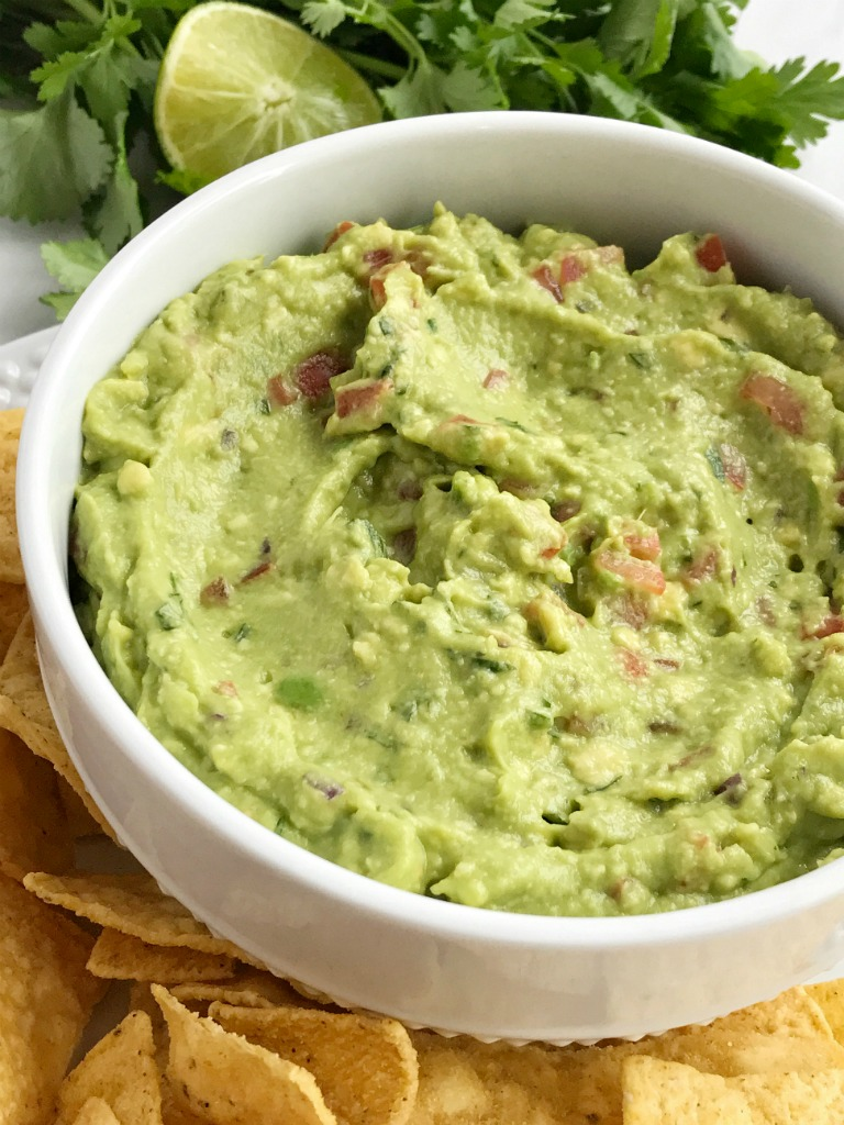 Salsa verde guacamole is loaded with tomato, cilantro, smashed avocado, jalapeno and salsa verde. Serve with tortilla chips for a delicious appetizer and a fan favorite for a game day party   Together as Family #guacamole #superbowlrecipes #appetizerrecipes #salsaverde #salsaverderecipes #healthyrecipes #recipeoftheday
