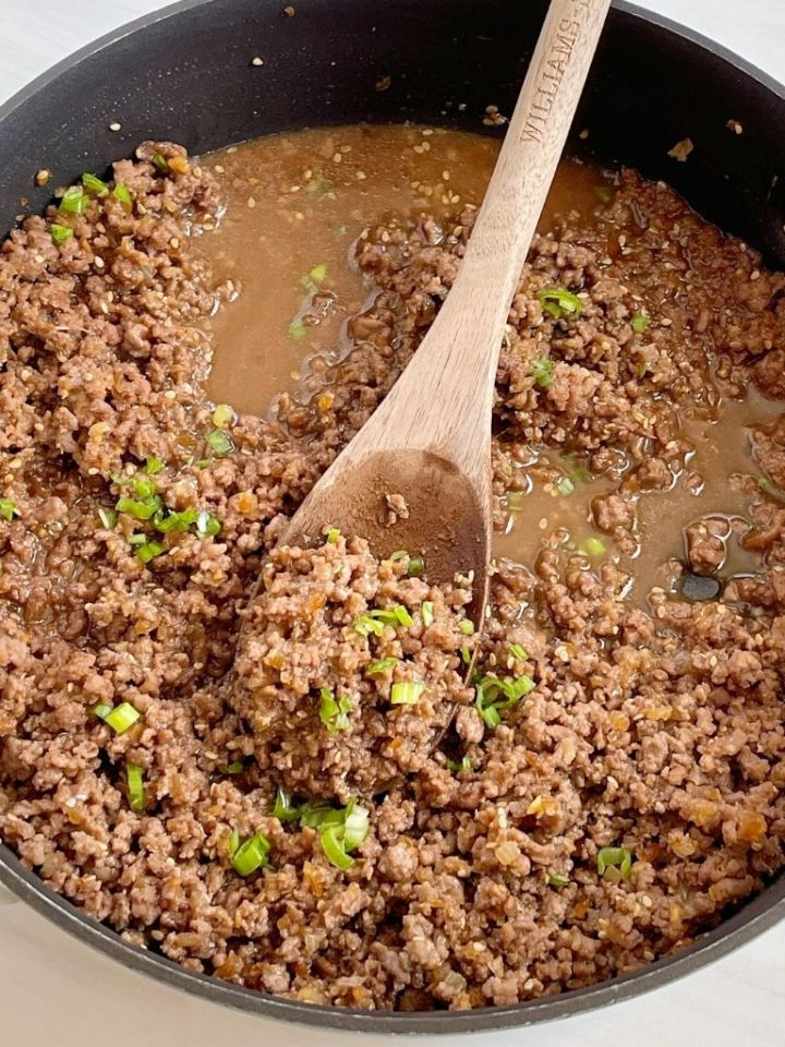 A skillet pan of ground beef teriyaki topped with green onions.
