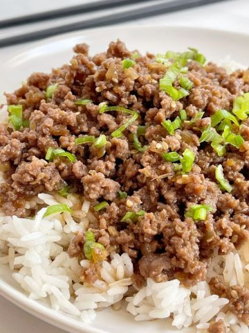 A white plate with rice and ground beef with teriyaki. Chopsticks in the background.