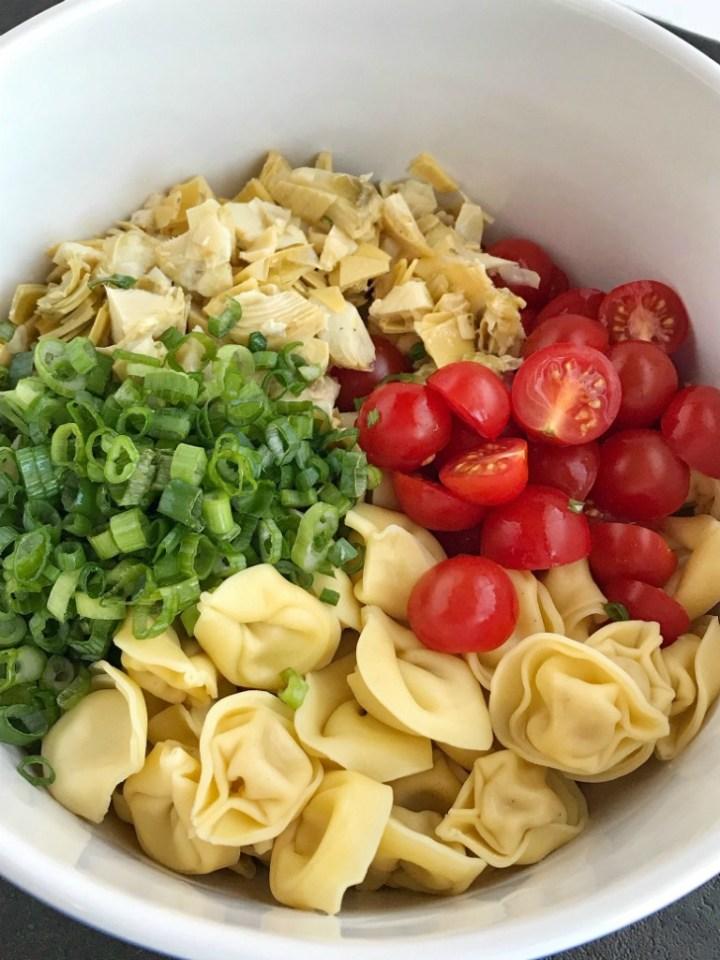 Creamy Tortellini Artichoke Pasta Salad | Creamy tortellini artichoke pasta salad requires only 5 ingredients! It's so quick & easy and perfect for a BBQ, picnic, light lunch, or a side dish. Marinated artichoke hearts, cherry tomatoes, green onions, tortellini, and creamy Italian dressing create a delicious pasta salad #pastasaladrecipes #artichokerecipes #tortellini