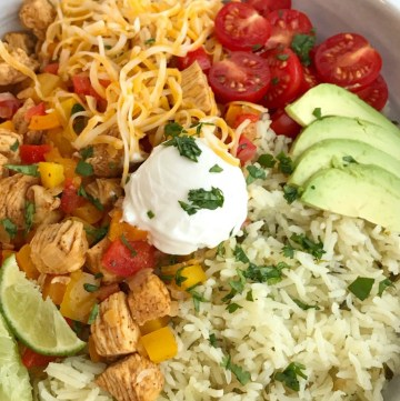 Chicken Fajita Burrito Bowls | Burrito Bowls | Mexican Food | Cinco de Mayo Recipes | Dinner | Chicken fajita burrito bowls are so easy to make at home! No need to go to restaurant for a burrito bowl anymore. Chicken, onion, peppers and seasonings cook in a skillet pan while cilantro lime rice simmers on the stove top. Serve with all your favorite burrito toppings for a healthy and delicious dinner that everyone can make their own of. #easydinnerrecipes #cincodemayo #burritobowls