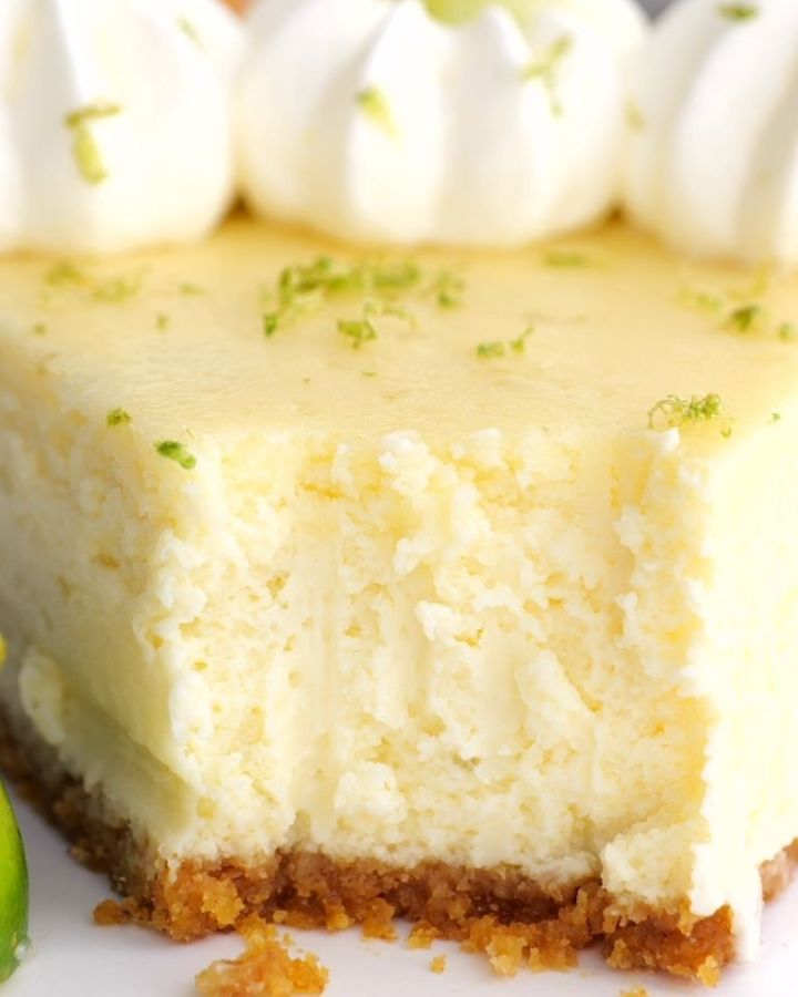 A close picture of a cheesecake with a bite taken out the front to show the texture of the creamy cheesecake.