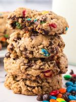 Stack of monster cookies with a bite taken out of the top cookie.