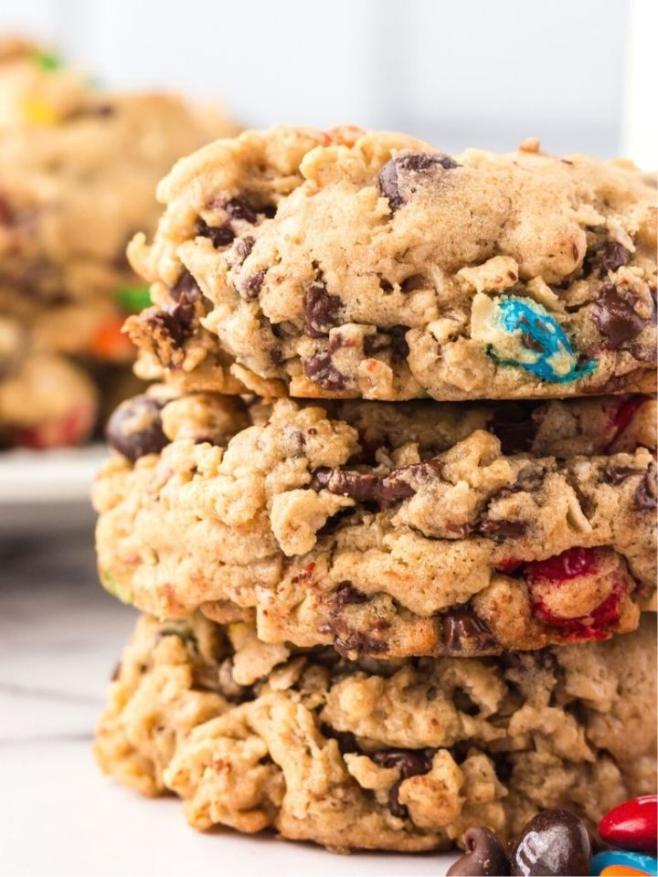 Stack of monster cookies with cookies in the background.