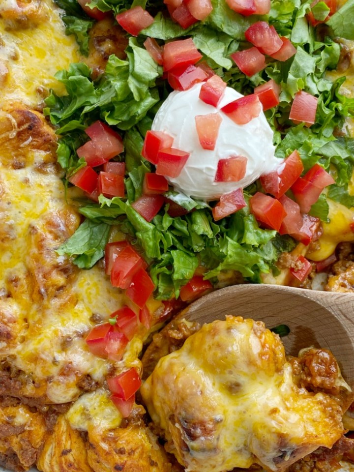 Taco biscuit bake is an easy & simple dinner recipe with refrigerated biscuit dough smothered in a beefy taco mixture and topped with melted cheese.