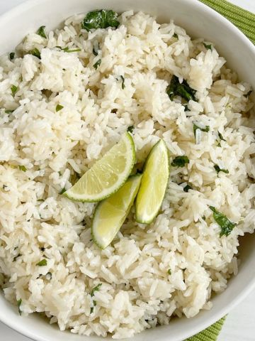 A white bowl of cilantro lime rice garnished with lime wedges on top.