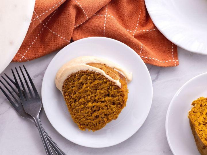 Pumpkin bundt cake slice on a plate with a fork.