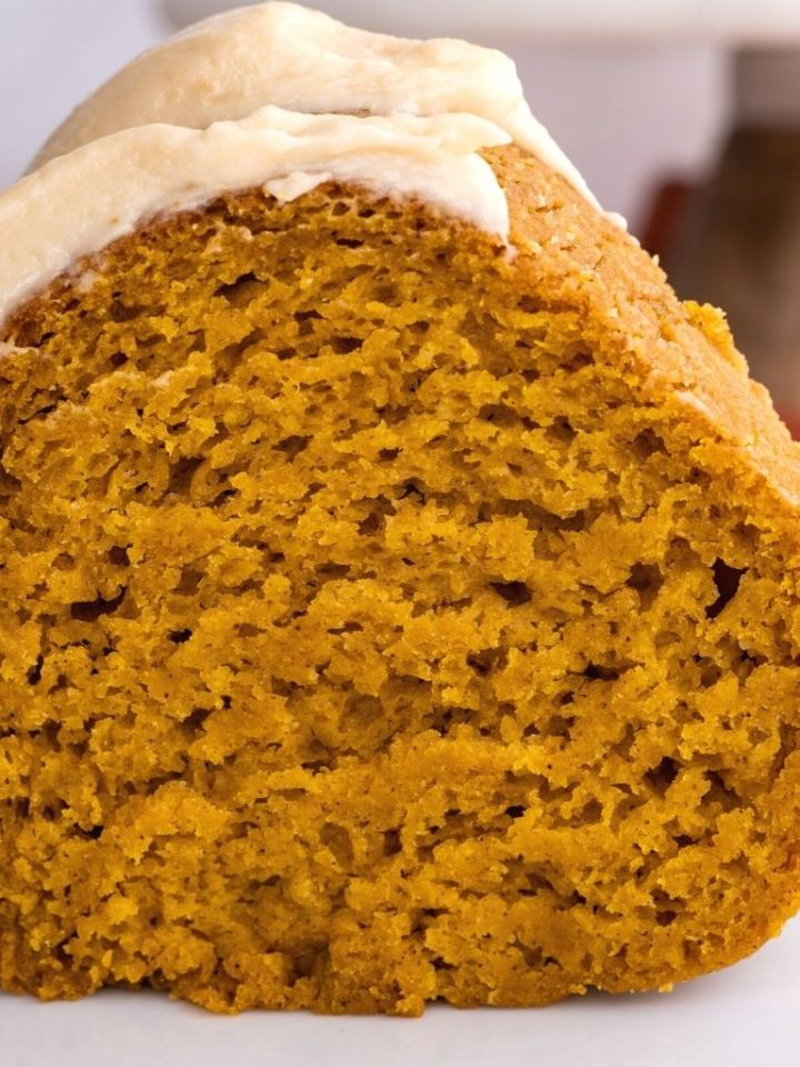 Picture of a slice of pumpkin bundt cake topped with caramel frosting on top of a white plate.