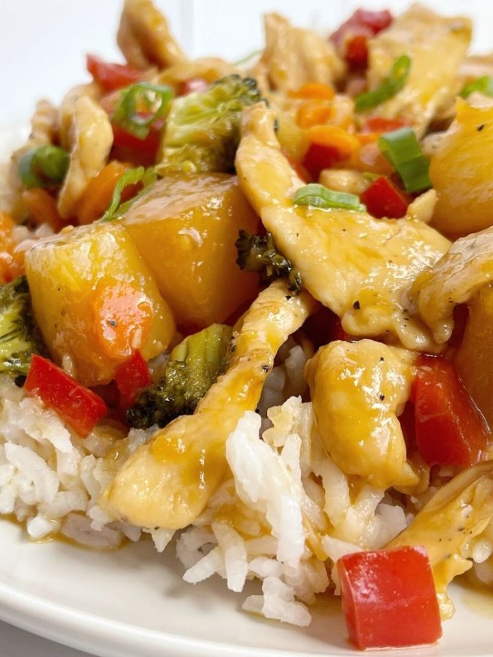 A plate with white rice and some chicken stir fry on top.
