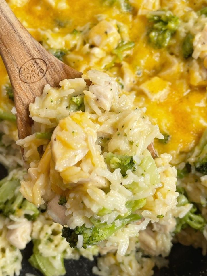 A wooden spoon with a scoop of cheesy chicken broccoli and rice.