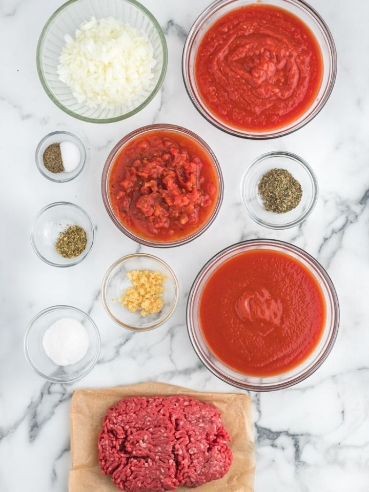 Ingredients needed to make spaghetti meat sauce. Each ingredient is inside it's own bowl.