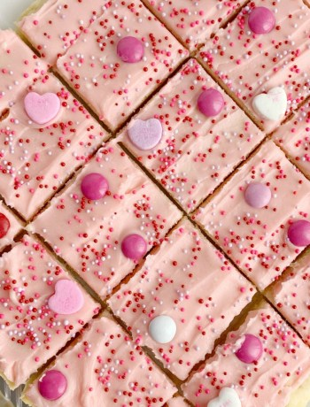 Valentines Day Sugar Cookie Bars | Sugar Cookie Bars | Valentines Dessert Recipes | Valentines day sugar cookie bars are the perfect sweet treat to celebrate with. Soft, thick sugar cookie bars frosted with the best pink frosting ever! Decorate with all your favorite Valentines candy and enjoy. #holidayrecipes #valentinesdayrecipes #valentinesday #dessert #sugarcookiebars