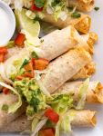 Chicken flautas on a white tray topped with lettuce, tomato, and guacamole.
