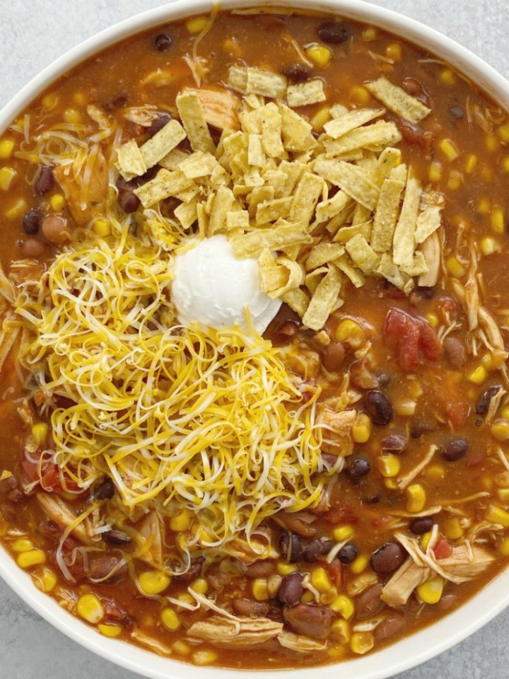 Taco Ranch Chicken Chili cooks in the slow cooker and only needs a few pantry staple ingredients! It's a dump & go chili with chicken , vegetables, beans, and lots of flavor. No chopping or prep work needed for this easy chili recipe.