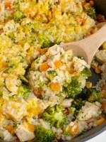 CHEESY CHICKEN AND RICE is made in only one skillet pan! Chunks of seasoned chicken, carrots, broccoli, and rice simmer in chicken broth. Sprinkle with cheese and serve this delicious dinner.