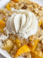 Peach dump cake on a white plate with ice cream melting on top.