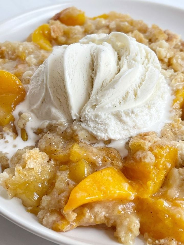 Plate of peach dump cake with ice cream on top.